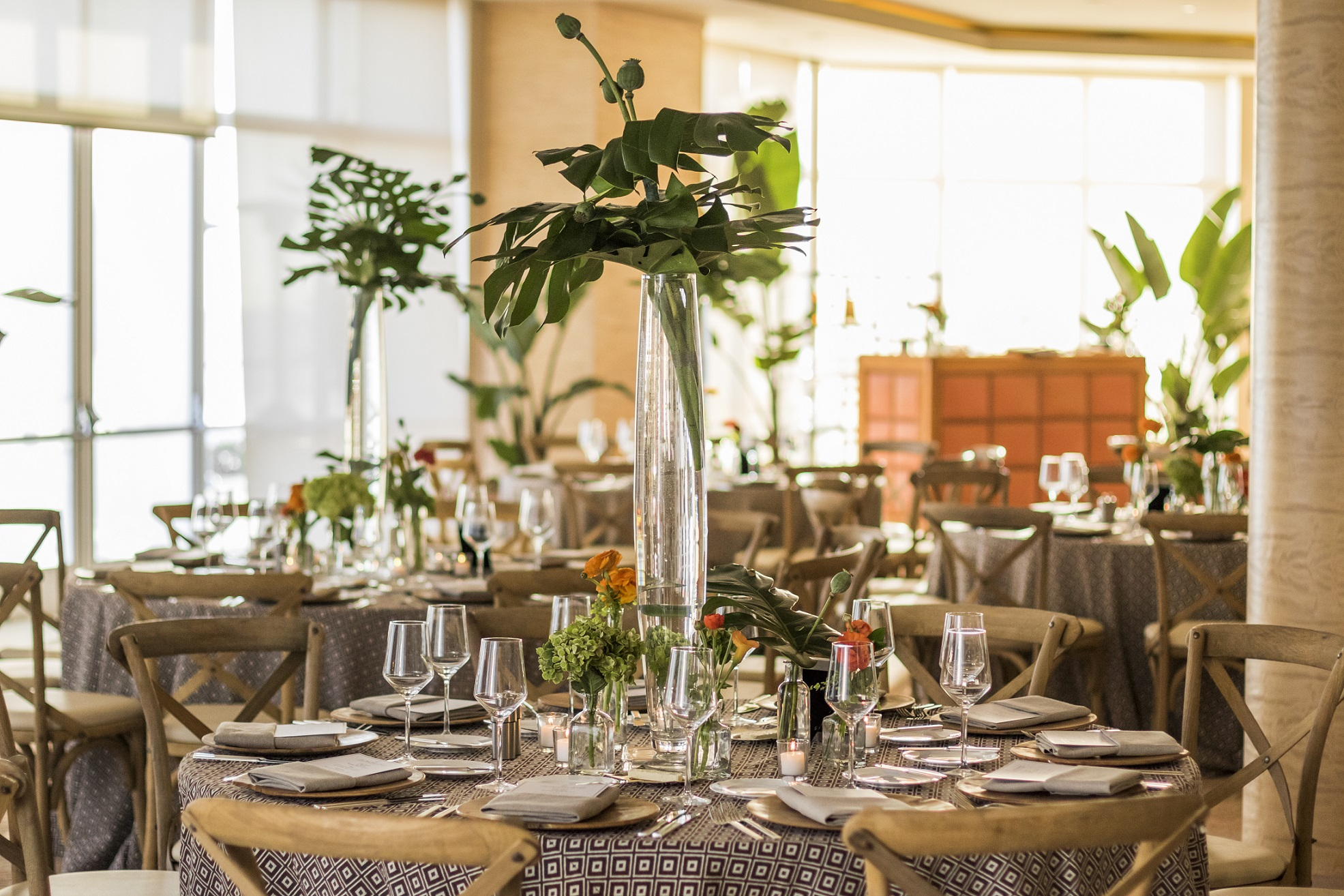 Elegant Tropical Centerpieces top neutral tables for this event design