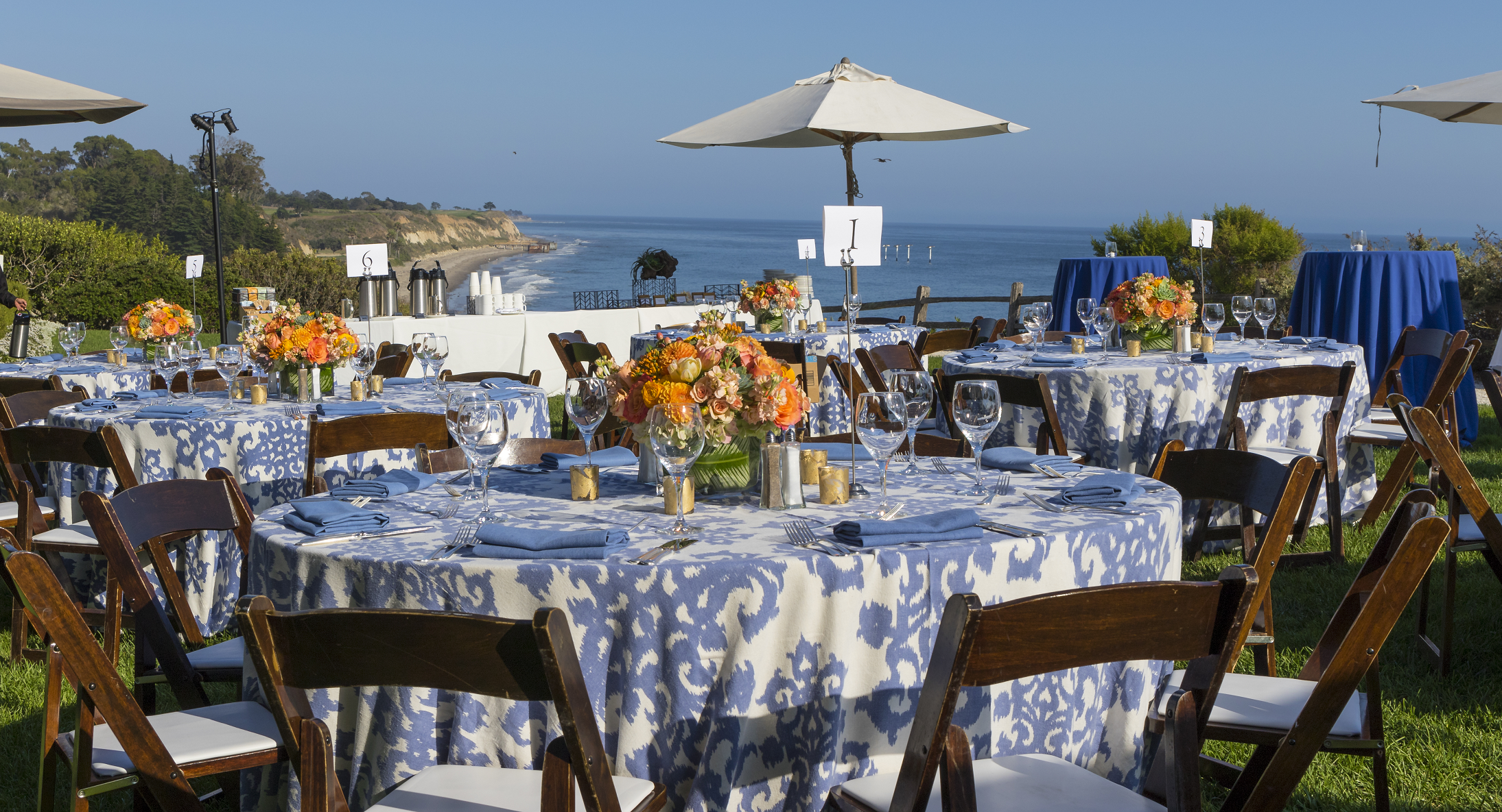 Coastal View event with blue casablanca linen and bright orange centerpieces
