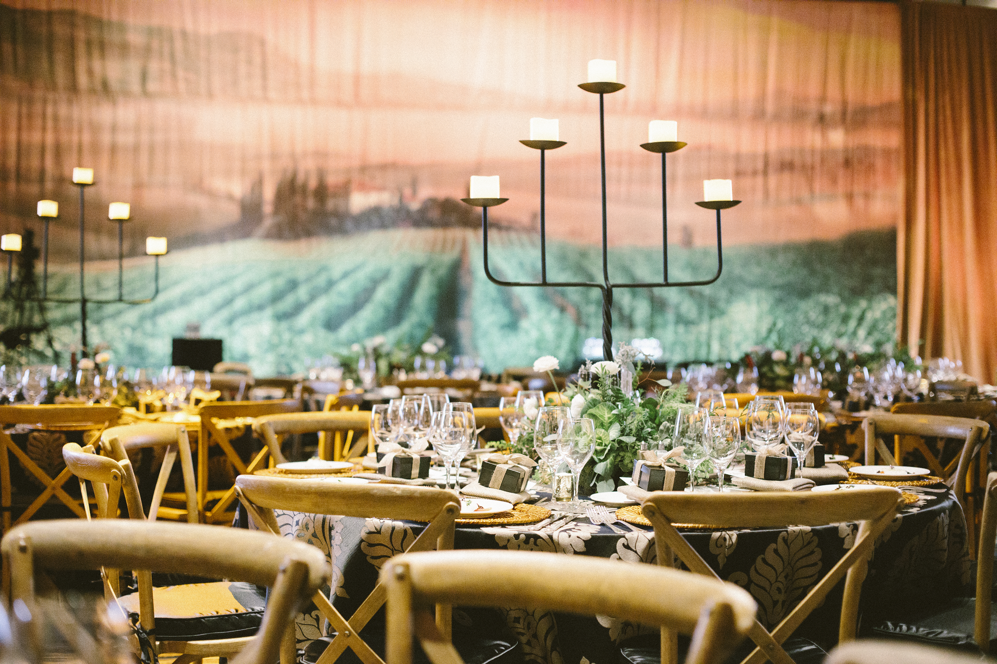 An awards event inspired by the wine country featuring natural wood chairs, centerpieces featuring greenery and wine bottles