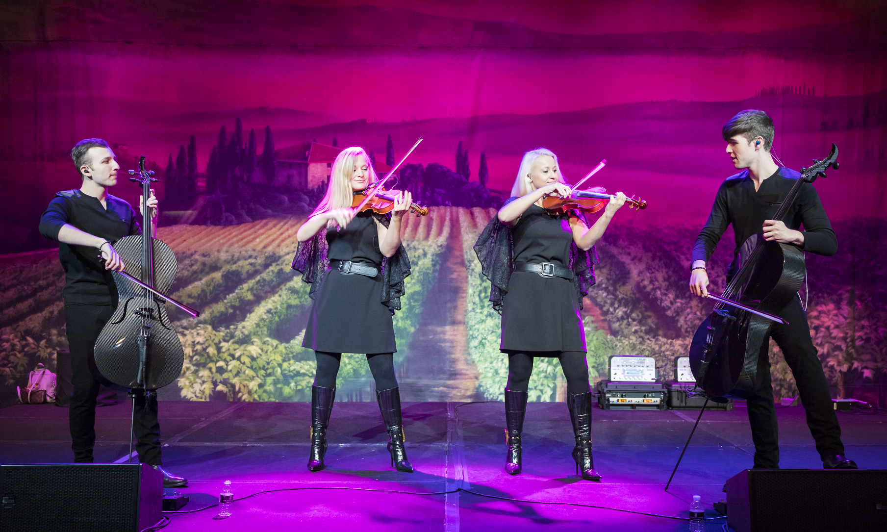 A violin duo and cello duo performance on a stage in front of a wine country background