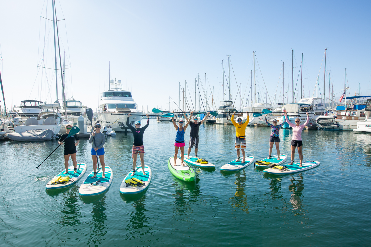A group is Stand up Paddle boarding (SUP) in the Santa Barbara Harbor