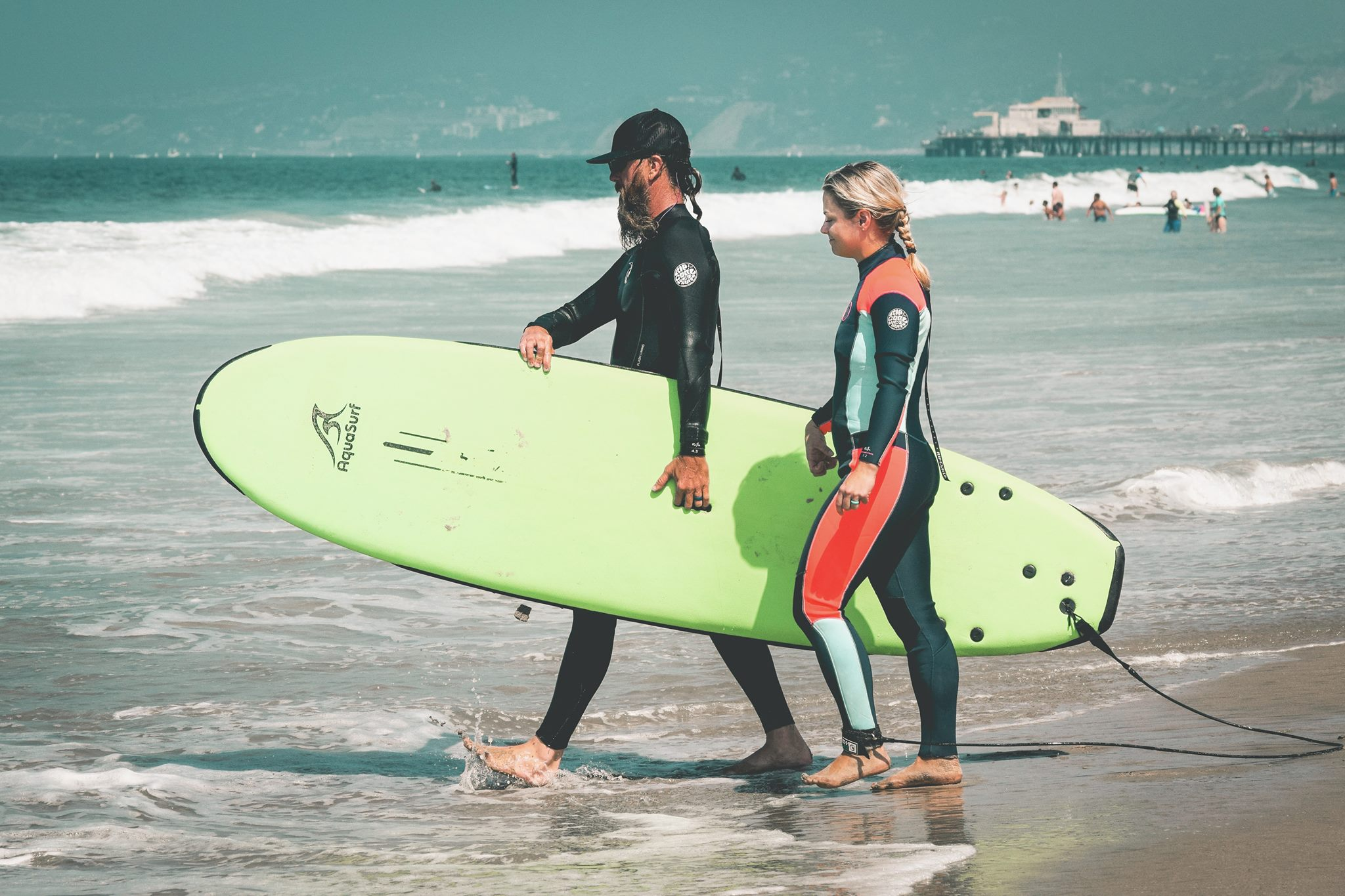 A new surfer and instructor walking into the surf with a neon green surfboard