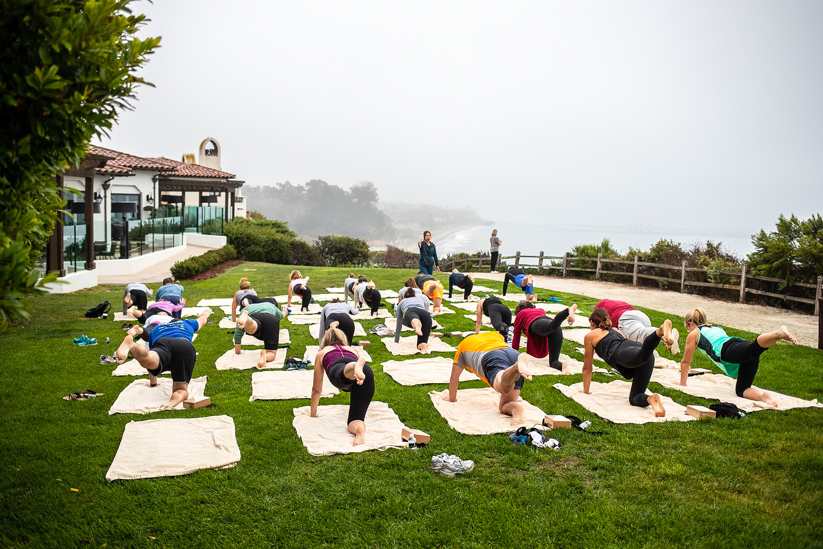 A group enjoys a yoga class in the grass on an ocean front bluff on a foggy morning